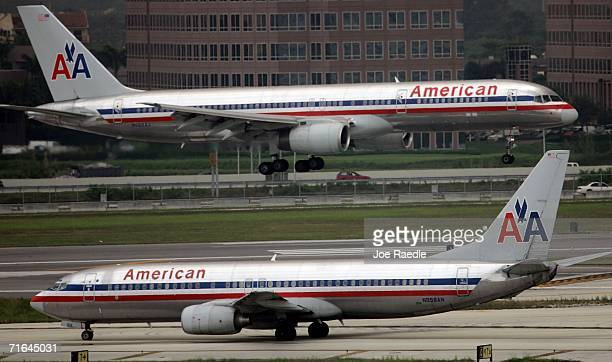 An American Airlines plane lands next to one waiting to take off on the tarmac at the Miami International Airport August 14 2006 in Miami Florida...
