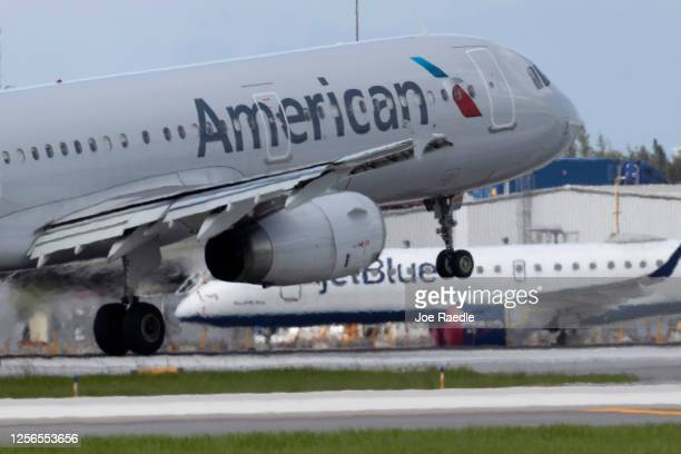 An American Airlines plane lands on a runway near a parked JetBlue plane at the Fort Lauderdale-Hollywood International Airport on July 16, 2020 in...