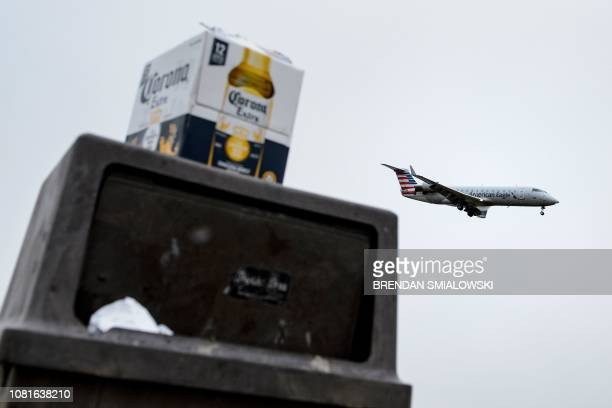 An American Airlines plane passes over an overflowing trash can with a Corona Beer box on it in Gravelly Point Park while landing at Ronald Reagan...