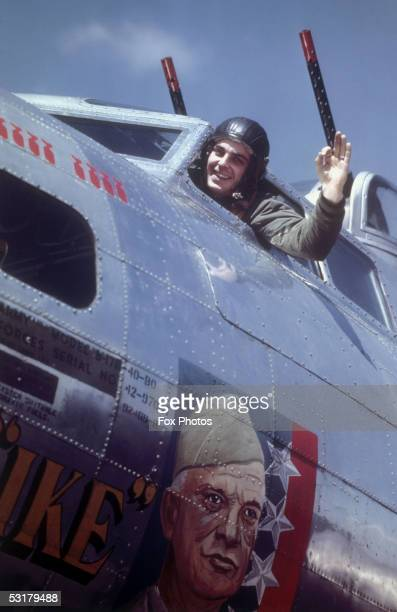 An American airman stationed in Britain waves from the cockpit of a B17 Flying Fortress bomber emblazoned with a picture of US General Dwight D...