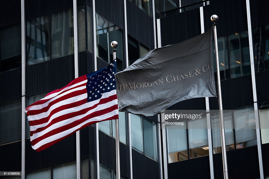 An American and a JPMorgan Chase & Co. flag fly outside the company's headquarters in New York, U.S., on Friday, Oct. 7, 2016. JPMorgan Chase & Co. is scheduled to release earnings figures on October 14. Photographer: Mark Kauzlarich/Bloomberg via Getty Images