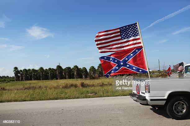 An American and Confederate flag fly from a vehicle during a rally to show support for the flags on July 11 2015 in Loxahatchee Florida Organizers of...