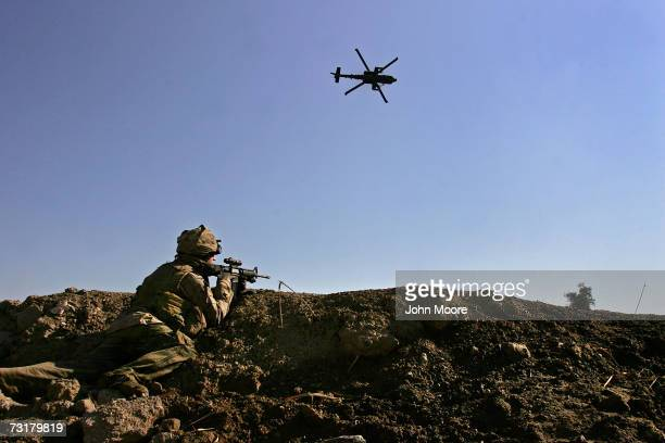 An American Apache helicopter proves air support as a US Marine takes aim after being fired upon by insurgents near the Euphrates River February 2...