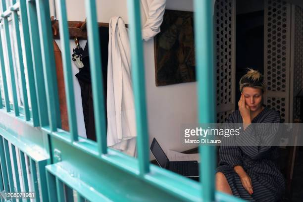 An American art dealer who has just woken up is seen through the grates of her balcony on March 22 2020 in Rome Italy As Italy extends its nationwide...