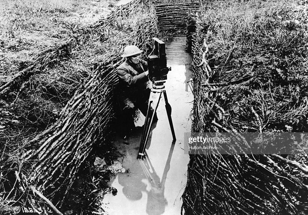 An American cinematographer sets up his camera in a water-filled trench.