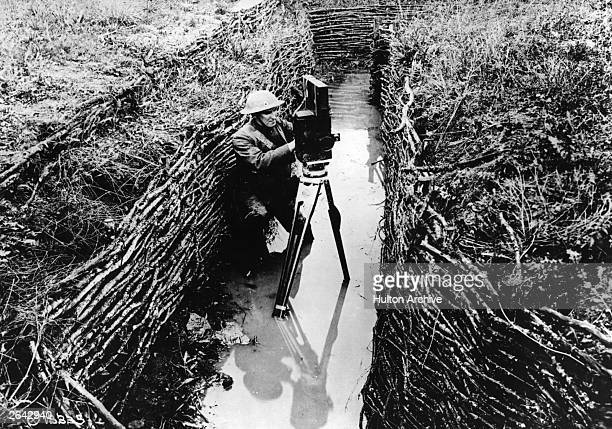 An American cinematographer sets up his camera in a waterfilled trench