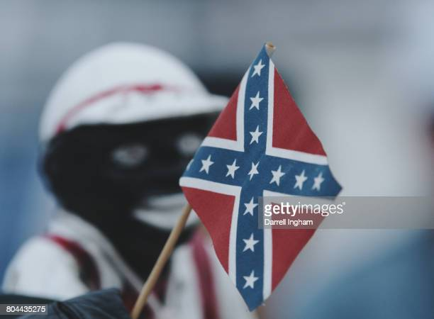 An American Civil War era miniature Stars and Bars Confederate battle flag is seen next to a Black Lawn Jockey statue during the 1997 NASCAR Winston...