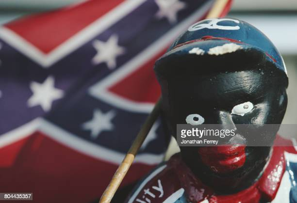 An American Civil War era miniature Stars and Bars Confederate battle flag is seen next to a Black Lawn Jockey statue during the 1998 NASCAR Winston...