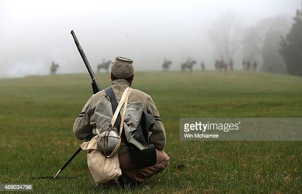 An American Civil War reenactor dressed as a member of the North Carolina 26th infantry watches Union cavalry take their position during a...