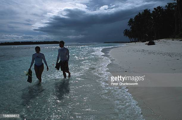 An American couple who are part of a surf boatcharter take time to explore one of the thousands of goldensand beaches that ring the Mentawai Islands...