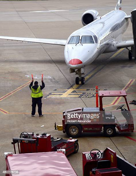 An American Eagle Airlines passenger jet is directed to the gate by a ground crew member at Dallas/Fort Worth International Airport in Dallas Texas