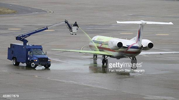 An American Eagle jet is sprayed with deicing compound on a DFW Airport runway in Fort Worth Thursday Dec 5 2013 A winter weather storm is heading...