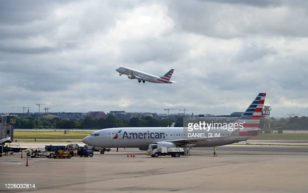 An American Eagle plane takes off while an American Airlines plane approaches a gate at Ronald Reagan Washington National Airport on July 10 in...