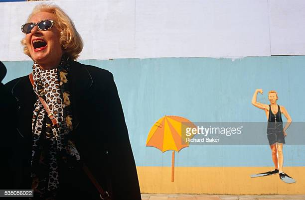 An American expatriate living in Monaco laughs at a joke from an unseen person while standing near her apartment in front of a beach mural on the...