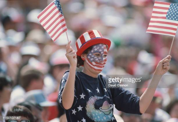 An American fan waves two United States flags during the opening ceremony for the XXIII Olympic Games on 28 July 1984 at the Los Angeles Memorial...