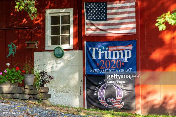 An American flag, a Trump re-election flag, and a QAnon flag are displayed on a barn in central Pennsylvania.