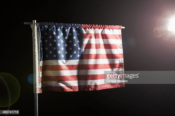 An American flag against a black background, spot lit