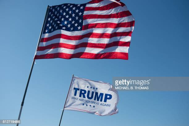 An American Flag and a Donald Trump flag wave outside a Donald Trump rally at Millington Regional Jetport on February 27 2016 in Millington Tennessee...