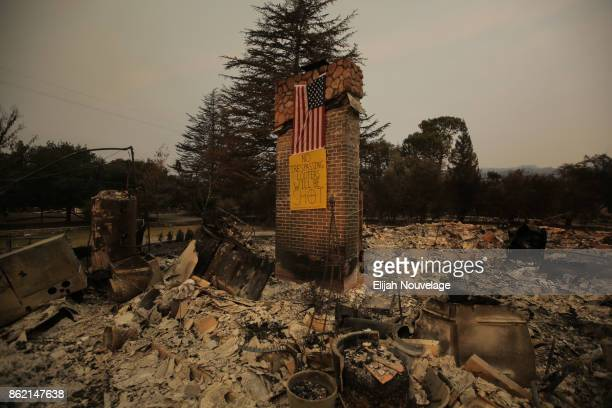 An American flag and a handmade antilooter sign are seen on a chimney in the remains of a home on October 16 2017 in Glen Ellen California At least...
