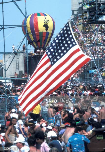 An American flag and a hot air balloon are shown flying in the air during Live Aid in Philadelphia on July 13, 1985.