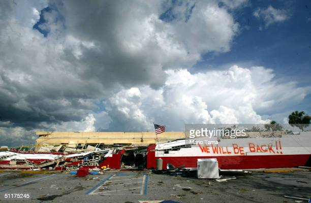 """An American flag and a makeshift sign reading """"We Will Be Back"""" are seen on a destroyed Ace Hardware store August 15, 2004 in Port Charlotte,..."""