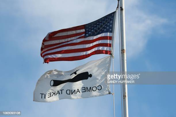 An American Flag and a replica flag from the battle at the Alamo standing atop Patriot Point along the USMexico border in Campo California on...