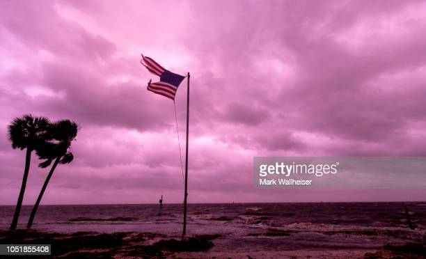 An American flag battered by Hurricane Michael continues to fly in the in the rose colored light of sunset at Shell Point Beach on October 10 2018 in...