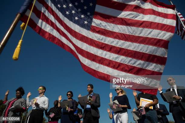An American flag billows in the wind as immigrants stand and take the oath of allegiance to the United States during a naturalization ceremony at...