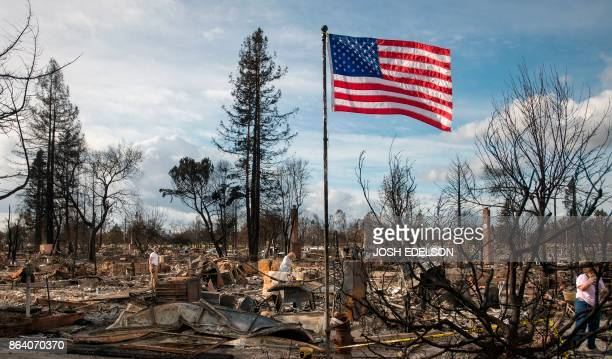 An American flag blows in the wind as residents sift through the remains of their burned homes in the Coffey Park area of Santa Rosa California on...