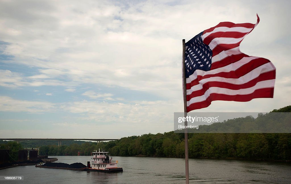 An American flag blows in the wind on the back of the Consol Energy Champion Coal tow boat as it makes its way down the Monongahela River transporting coal, outside Pittsburgh, Pennsylvania, U.S., on Wednesday, May 15, 2013. Coal's prospects are improving after its share of U.S. power generation fell last year to 34 percent, the lowest since at least 1973, Energy Department data show. Hotter temperatures this summer that prompt American households to use more air conditioning will boost demand for coal and the railroads that ship it. Photographer: Ty Wright/Bloomberg via Getty Images