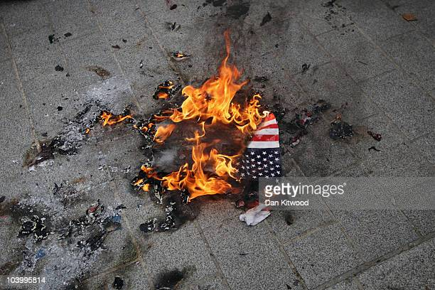 An American flag burns outside the American Embassy during a protest in Grosvenor Square on September 11 2010 in London England US Controversial...