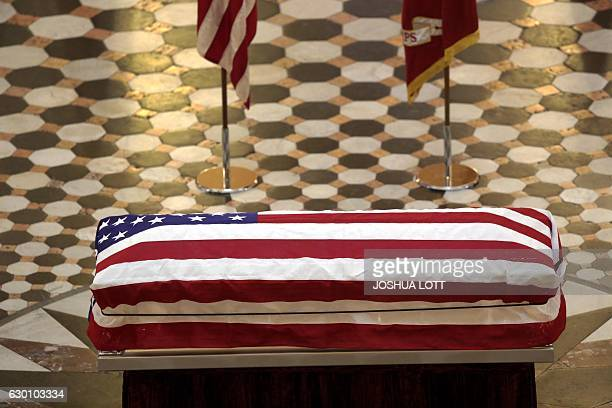 An American flag covers the casket of former astronaut and US Senator John Glenn is seen, as he lays in state at the Ohio Statehouse on December 16,...