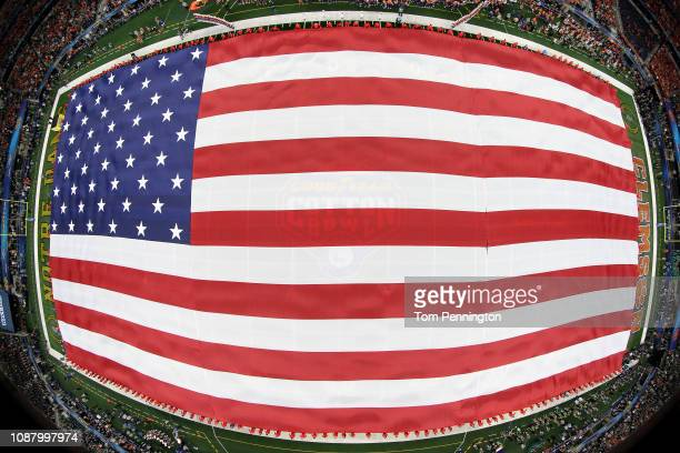 An American flag covers the field as the national anthem is performed before the College Football Playoff Semifinal Goodyear Cotton Bowl Classic...
