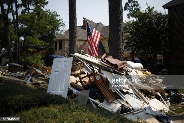 An American flag flies above a pile of flood damaged debris stripped from inside a house that was flooded by Hurricane Harvey in Spring Texas US on...