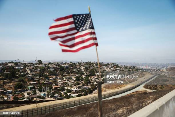 An American flag flies along a section of the USMexico border with the Mexican city of Tijuana in the background on July 16 2018 in San Diego...