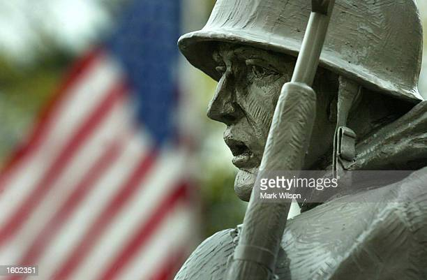 An American flag flies at half staff near a statue of a soldier at the Korean War Memorial on Veterans Day November 11 2002 in Washington DC