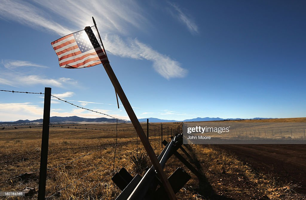 An American flag flies at the U.S.-Mexico border on February 26, 2013 near Sonoita, Arizona. The Federal government has increased the Border Patrol presence in Arizona, from some 1,300 agents in the year 2000 ro 4,400 in 2012. The apprehension of undocumented immigrants crossing into the U.S. from Mexico has declined during that time from 600,016 in 2000 to 123,000 in 2012.