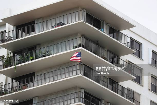 An American flag flies from a condo balcony in the building that has a possible connection to alleged bomber Cesar Sayoc and his mother on October 26...