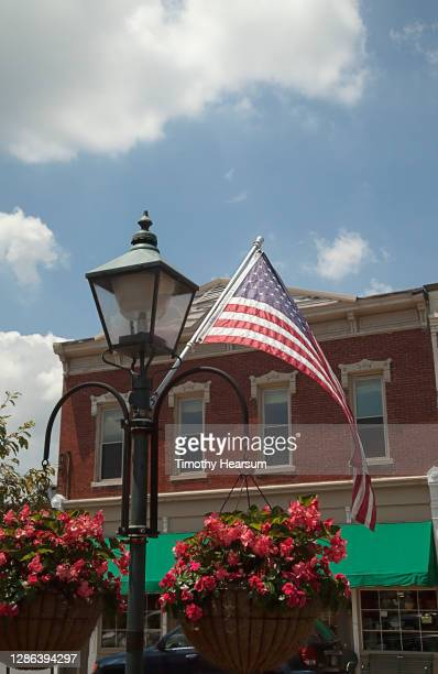 an american flag flies from a lamp post in a small town - timothy hearsum stock pictures, royalty-free photos & images