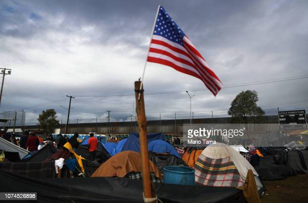 An American flag flies in a temporary shelter set up for members of the 'migrant caravan' with a section of the USMexico border fence in the...