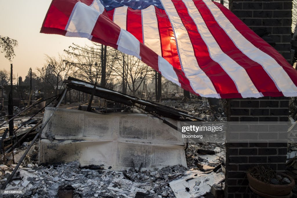 An American flag flies in front of residences burned by wildfires in Santa Rosa, California, U.S., on Friday, Oct. 13, 2017. Wildfires that tore through northern California's iconic wine-growing regions have prompted evacuations of more than 20,000 people, killed 11 and damaged some of the most valuable vineyards and wineries in the U.S. About 1,500 commercial, residential and industrial structures were burned, and damage assessment teams have started accounting for the destruction. Photographer: David Paul Morris/Bloomberg via Getty Images