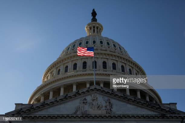 An American flag flies in front of the US Capitol during Senate impeachment proceedings in Washington DC US on Tuesday Jan 21 2020 President Donald...