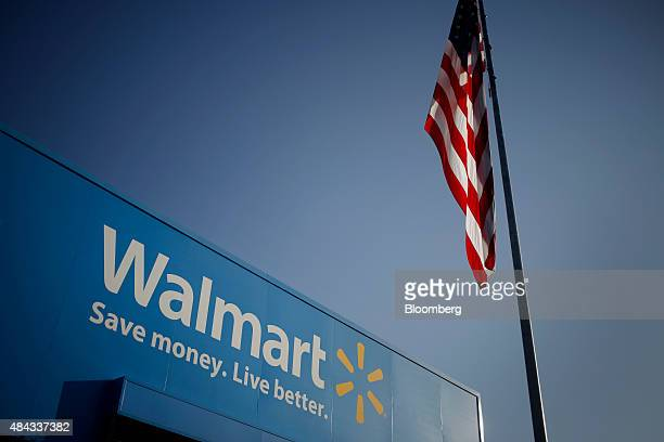 An American flag flies near signage displayed outside of the WalMart Stores Inc headquarters building in Bentonville Arkansas US on Wednesday July 29...