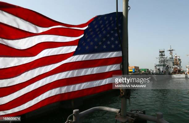 An American flag flies near US Navy boats docked at Bahrain's Salman port in the capital Manama on May 12 one day before the start of the biggest...