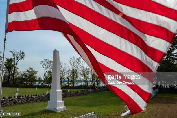An American flag flies next to a monument dedicated to Civil War soldiers who where once buried on Hart Island a former prison and Nike missile silo...