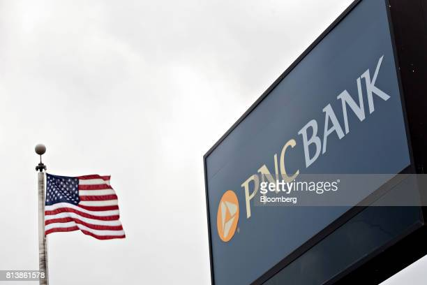 An American flag flies next to PNC Financial Services Group Inc signage displayed outside a bank branch in Morton Illinois US on Monday July 10 2017...