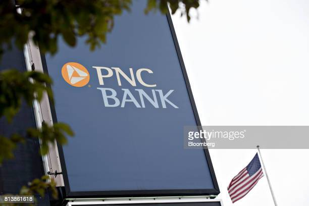 An American flag flies next to PNC Financial Services Group Inc signage displayed outside a bank branch in Peoria Illinois US on Monday July 10 2017...