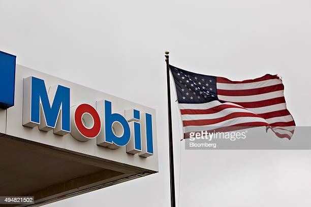 An American flag flies next to signage at an Exxon Mobil Corp gas station in Cherry Valley Illinois US on Wednesday Oct 28 2015 Exxon Mobil Corp is...