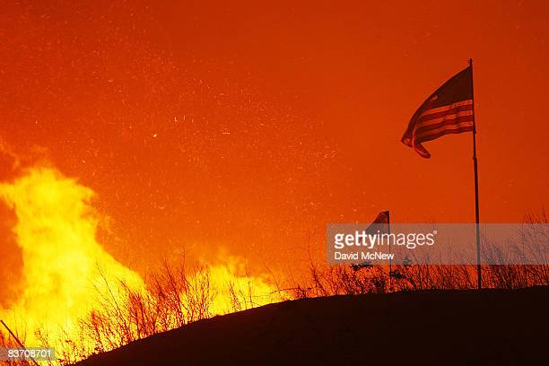 An American flag flies on a hill as fire draws close to homes on November 15 2008 in Yorba Linda California Strong Santa Ana Winds are destroying...