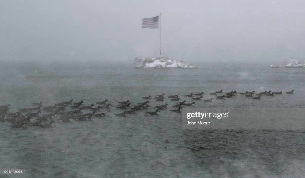 An American flag flies over an island as geese swim past on the Long Island Sound on January 4, 2018 in Milford, United States. The 'bomb cyclone' dumped heavy snows in New England as the storm system moved up the U.S. east coast.